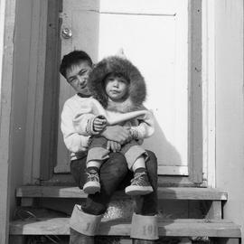 Photograph of Noah holding Billie Koneak on his lap in Fort Chimo, Quebec