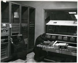 Photograph of two men installing equipment in the television control room
