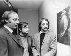 Photograph of three unidentified men looking at a photo