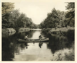 Photograph of two men netting a caught fish from a canoe on Mersey River at or near Jacques Landi...