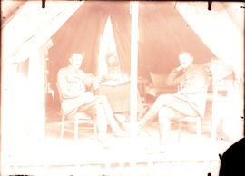 Two officers sitting inside of a tent
