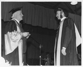 Photograph of Henry Hicks presenting a medal to a graduate