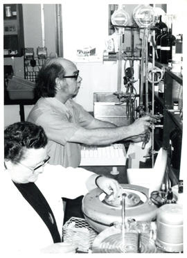 Photograph of two individuals in a laboratory working