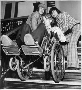 Photograph of Duncan Coates and Alex Fok lifting Larry Richards in a wheelchair