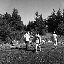 Photograph of a group of people walking on the shore on McNab's Island