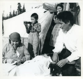 Photograph of four people and a dog by a tent in Davis Inlet, Newfoundland and Labrador