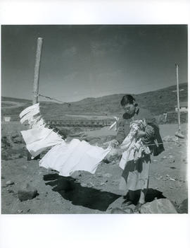 Photograph of an unidentified girl putting laundry on a clothesline