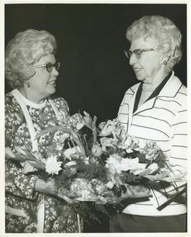 Photograph of Mrs. J. R. Longard presenting a floral arrangement to Mrs. F. R. MacAloney