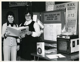 Photograph of Karen MacIntyre and Helen Patriquin demonstrating the Maritime Ambulatory Record System