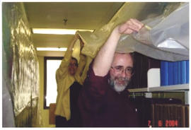 Photograph of Betty Sutherland and Patrick Ellis holding tarps after the Kellogg Library flood 2004