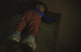 Photograph of a child with fur boots sleeping on the floor