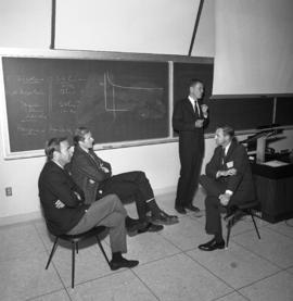 Photograph of four unidentified people in a classroom