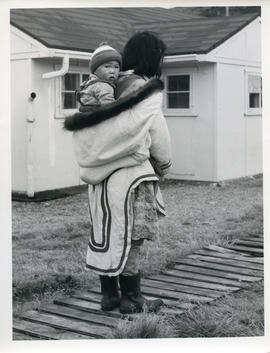Photograph of a woman carrying a baby in her parka in Sugluk, Quebec
