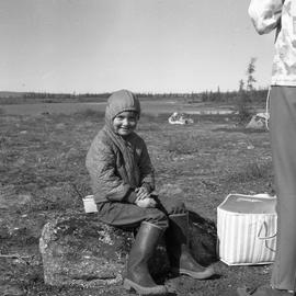 Photograph of Edward Koneak sitting on a rock in northern Quebec