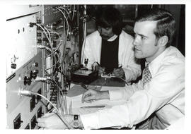 Photograph of two individuals running an experiment in a laboratory