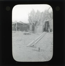 Photograph of people next to a hut