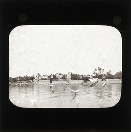 Photograph of unidentified buildings along riverbank