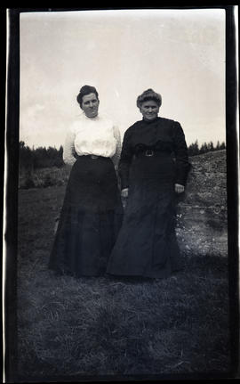 Two women leaning on a rock