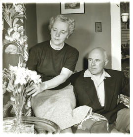 Photograph of Thomas Head Raddall watching his wife Edith arrange daffodils