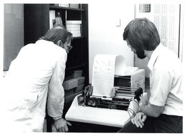 Photograph of two individuals in a laboratory waiting for results to print