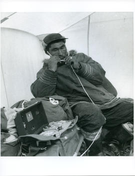 Photograph of an unidentified man with a tape recorder and headphones