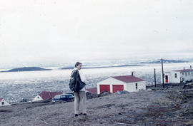 Photograph of Barbara Hinds walking toward some houses in Frobisher Bay, Northwest Territories