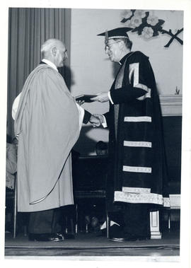 Photograph of Thomas Head Raddall receiving an honrary Doctor of Laws from Bishop W.E. Power at S...