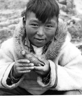 Photograph of a boy holding a carving in Cape Dorset, Northwest Territories