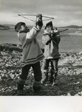 Photograph of two boys playing with toy bows and arrows in Cape Dorset, Northwest Territories