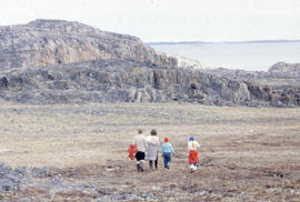Photograph of four people walking in Cape Dorset, Northwest Territories