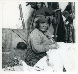 Photograph of a woman sitting on the ground near a tent in Davis Inlet, Newfoundland and Labrador