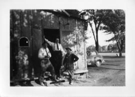 Photograph of three men standing in the door of a shed