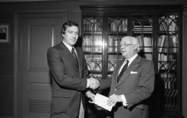 Photograph of an unidentified person presenting a cheque to Henry Hicks