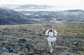 Photograph of Barbara Hinds walking up a hill near Frobisher Bay, Northwest Territories