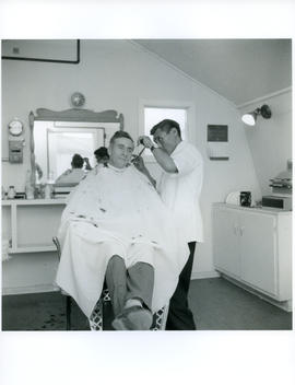 Photograph of an unidentified man having his hair cut by a barber