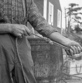 Photograph of an unidentified man tying a knot in a rope