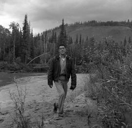Photograph of Dick Field walking by a river near Dawson City, Yukon