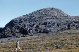 Photograph of a woman walking by a large rock formation in the eastern Canadian Arctic