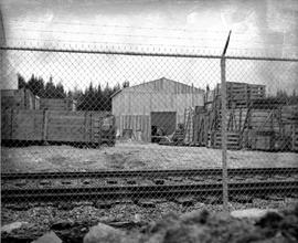 Photograph of crates and railroad tracks behind a fence