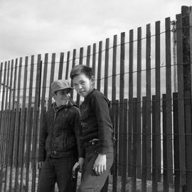 Photograph of Jackie Koneak and a friend standing by a fence in northern Quebec