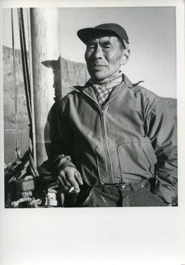 Photograph of Eetuk smoking a cigarette on a boat in Frobisher Bay, Northwest Territories