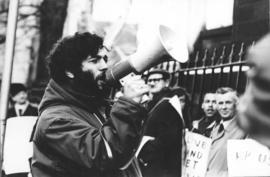 Photograph of Larry Katz, Graduate Student Council President, addressing a crowd in front of the ...