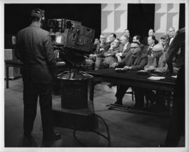 Photograph of a group of unidentified people in front of a Canadian Broadcasting Corporation camera