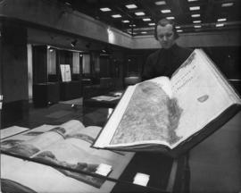 Photograph of Dalhousie archivist with large map book