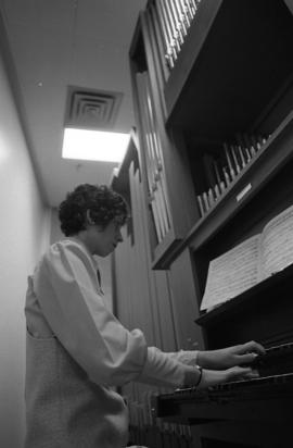 Photograph of an unidentified person playing a pipe organ