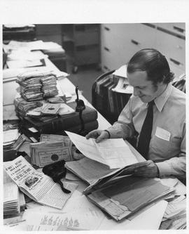 Photograph of Charles Armour looking at historical documents