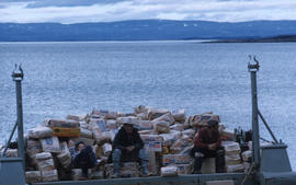 Photograph of three men sitting on a load of sugar in Frobisher Bay, Northwest Territories