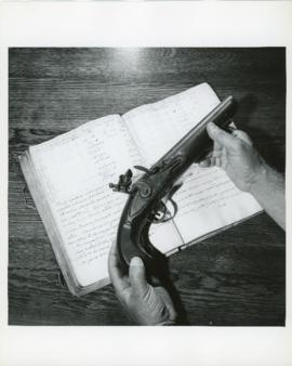 Photograph of a flintlock pistol held by Thomas Head Raddall over the logbook of the Spanish ship...