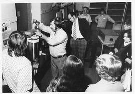 Photograph of Ralph Deveau demonstrating scientific equipment