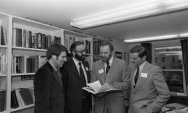 Photograph of four unidentified people looking at a book together